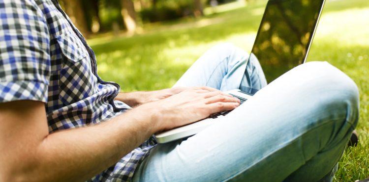 Mężczyzna z laptopem na kolanach